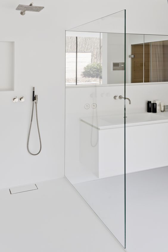 a minimalist white bathroom with a seamless shower, a long mirror and clean lines