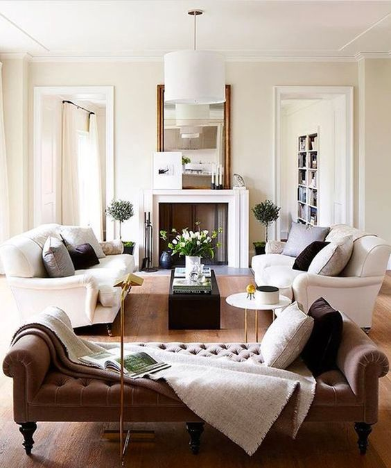 a refined living room with two white sofas and a tufted daybed for a luxurious feel