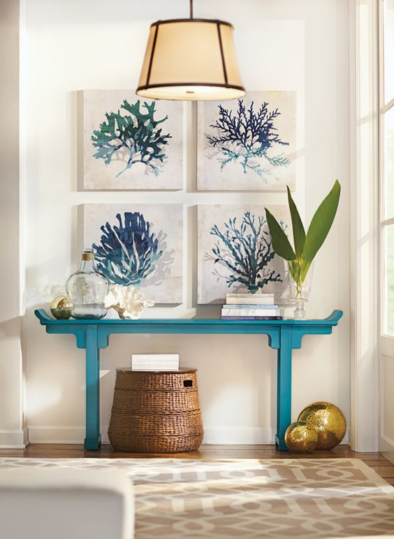 a turquoise console with a gallery wall of coral artworks, bottles and a basket