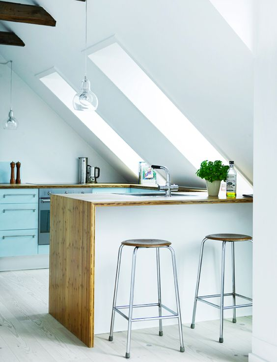 the kitchen island fits the attic angle and is surrounded with skylights