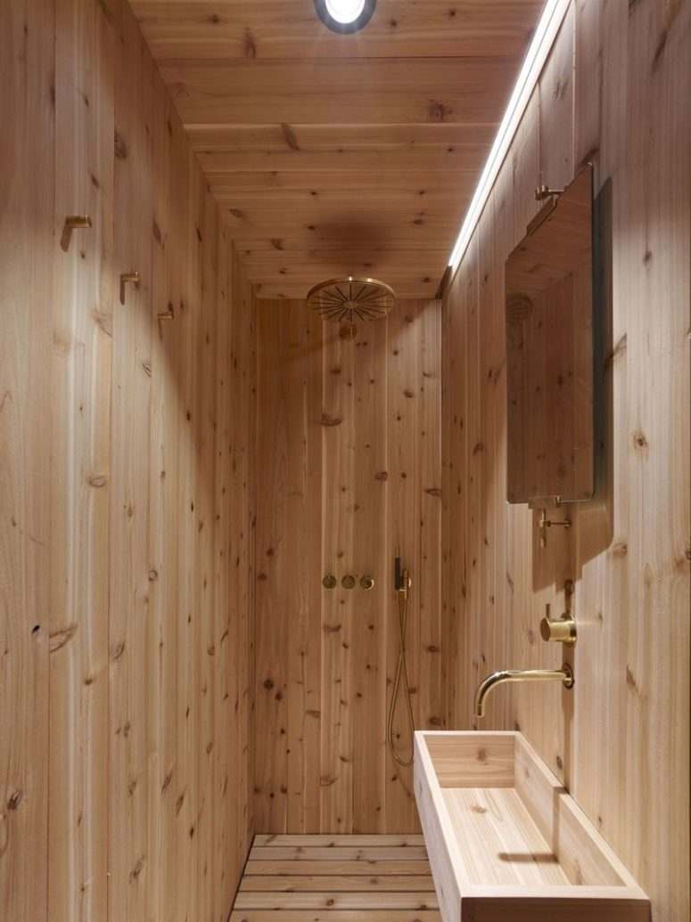 The bathroom is small, it features a shower and a sink, everything here is clad with wood