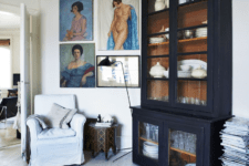 06 The black armoire is a vintage French piece and colorful art contrasts it