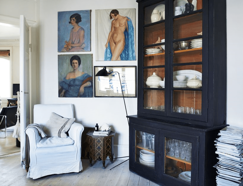 The black armoire is a vintage French piece and colorful art contrasts it