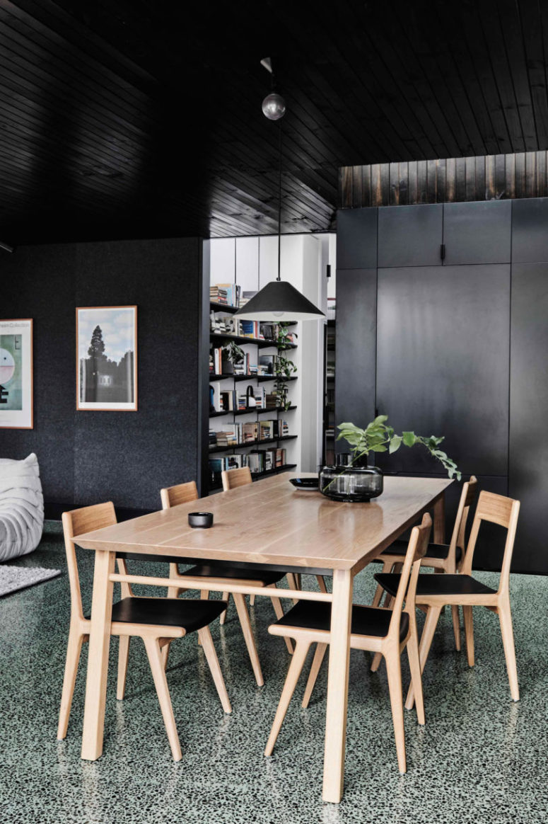 The dining space is done with a wooden table and chairs with black leather plus a black glass vase and a black pendant lamp