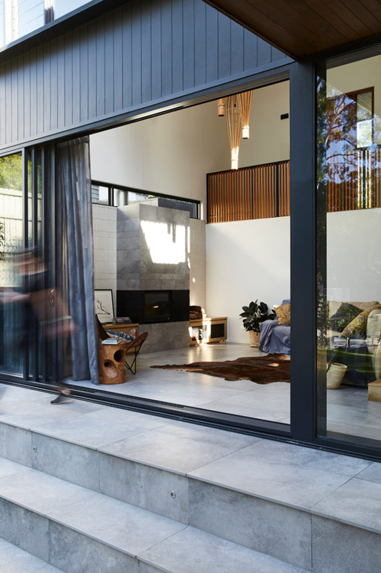 The living room is done with a modern built-in fireplace, comfy furniture and textiles, tiles are widely used here to make the space not so hot
