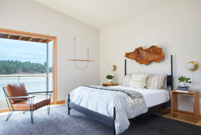 The master bedroom shows off an amazing view and a comfy bed with a rough wooden sculpture