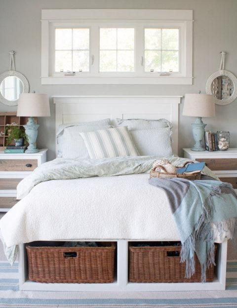 a beach cottage guest bedroom with a bed with storage baskets inside is a genius idea