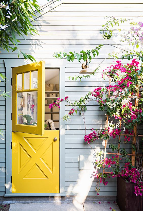 a bright yellow Dutch door, a grey wall and bold fuchsia blooms make this space wow