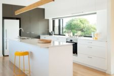 06 a contemporary white kitchen with touches of yellow and wood plus a window backsplash