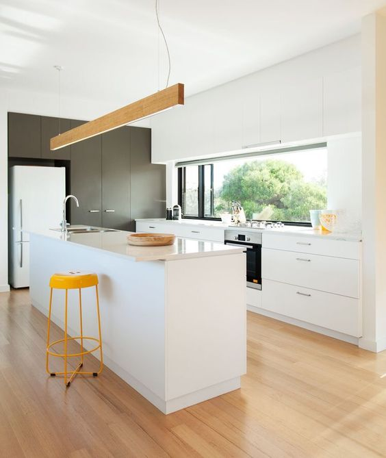 a contemporary white kitchen with touches of yellow and wood plus a window backsplash