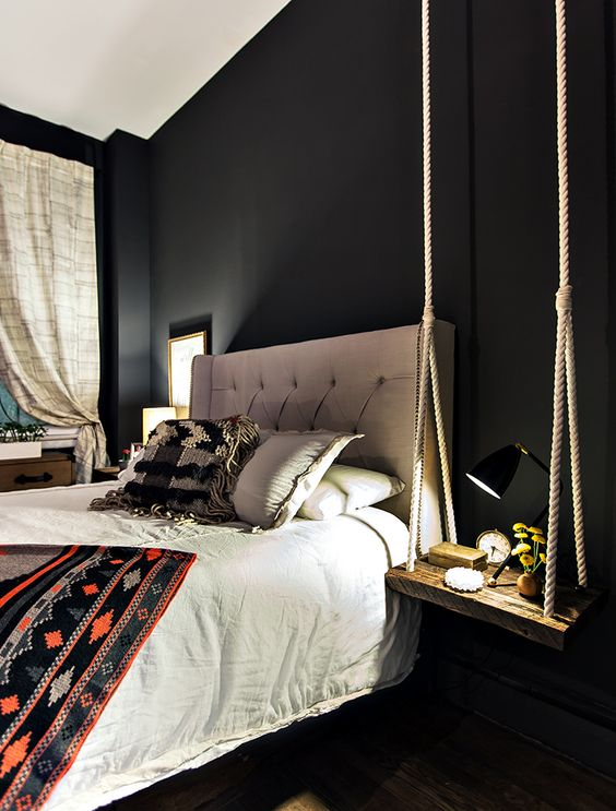 a cool modern bedroom with a boho feel and a swing-style bedside table of thick rope and a wooden piece