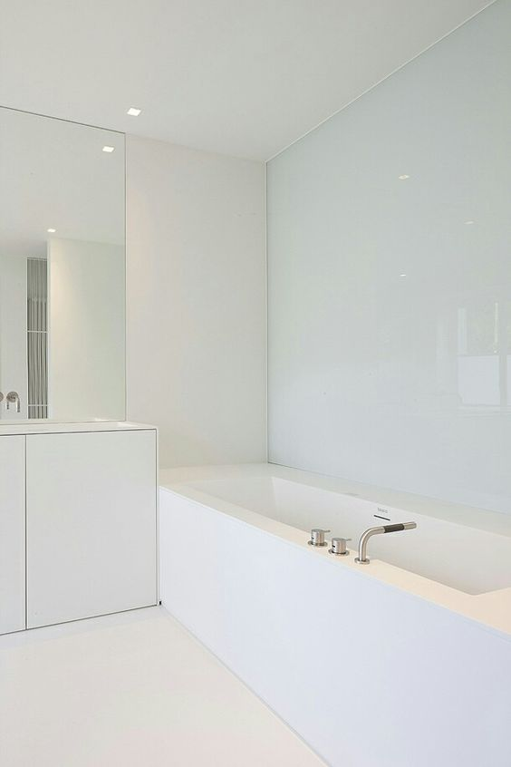 a minimalist white bathroom with a covered bathtub, a large mirror and a vanity