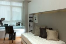 06 a small contemporary bedroom with a sleeping space, cabinets for storage and a glass windowsill