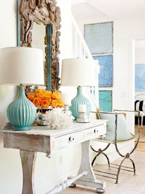 a whitewashed console table, a coral, turquoise lamps and a mirror clad with driftwood