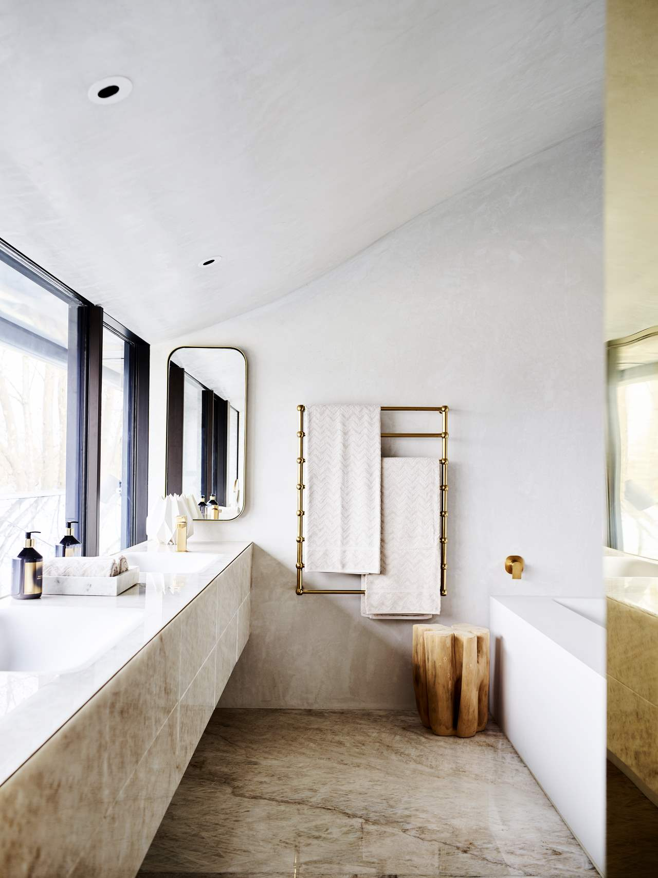 The bathroom is clad with quartz and brass spruces it up to look more glam