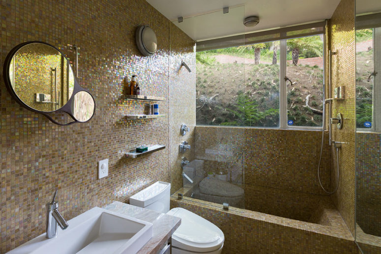 The bathroom is done with sparkling beige tiles and features a window