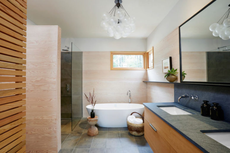 The bathroom is done with tiles and wooden touches
