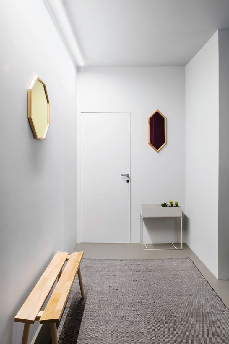 The entryway is done in white, with geometric mirrors and a textural rug plus a planter