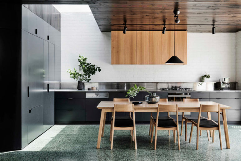 The kitchen features sleek black cabinets, upper light-colored wooden ones and some potted greenery