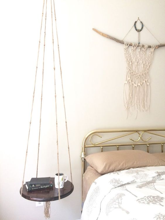 a boho bedroom with a hanging bedside table of dark stained wood and yarn that makes the space even more boho
