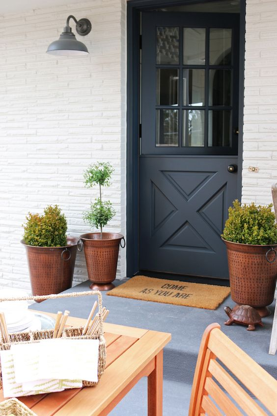 a chic entrance with hammered copper planters and a graphite grey Dutch door