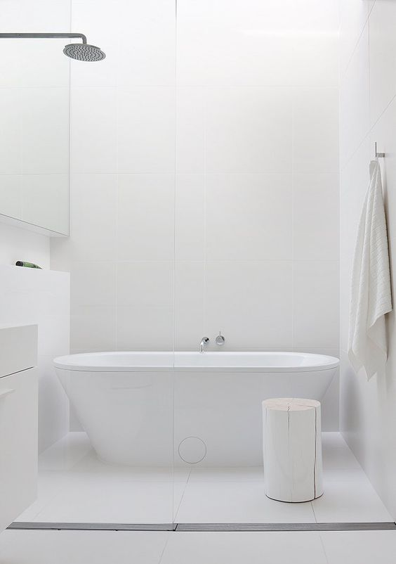 a chic white bathroom with a free-standing bathtub, a whitewashed stool and minimalist furniture