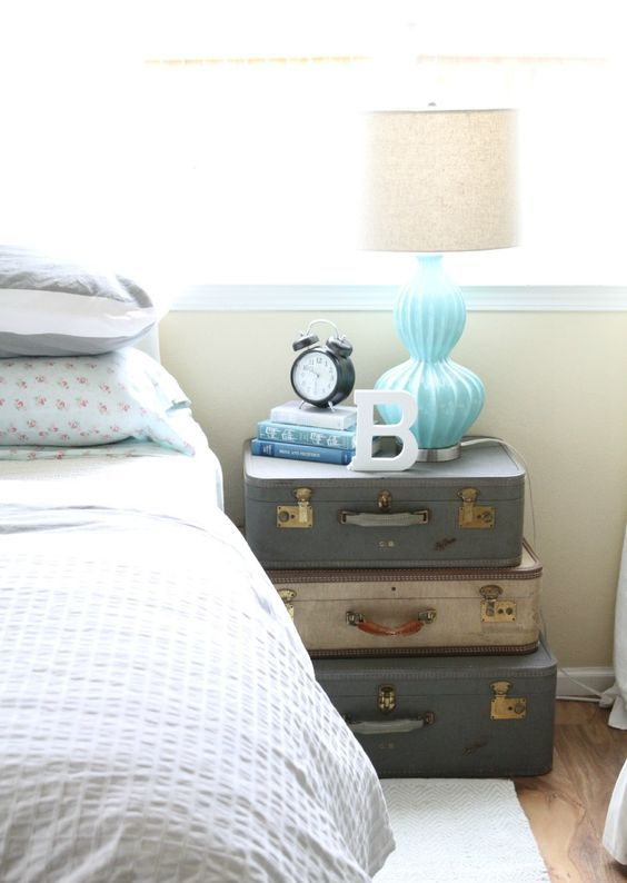 a stack of vintage suitcases highlights the rustic vintage style of the bedroom