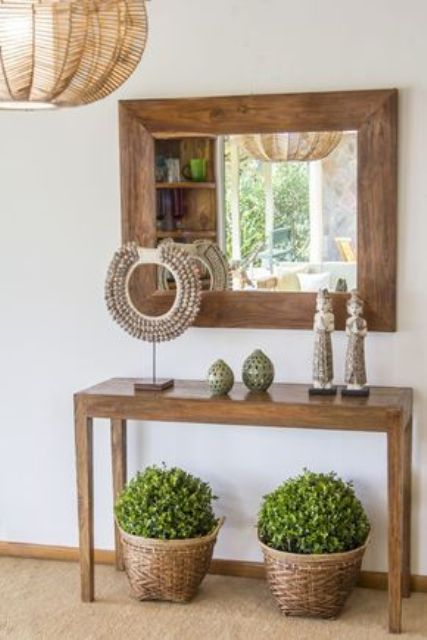 a wooden console with travel finds from the East and greenery in baskets under it