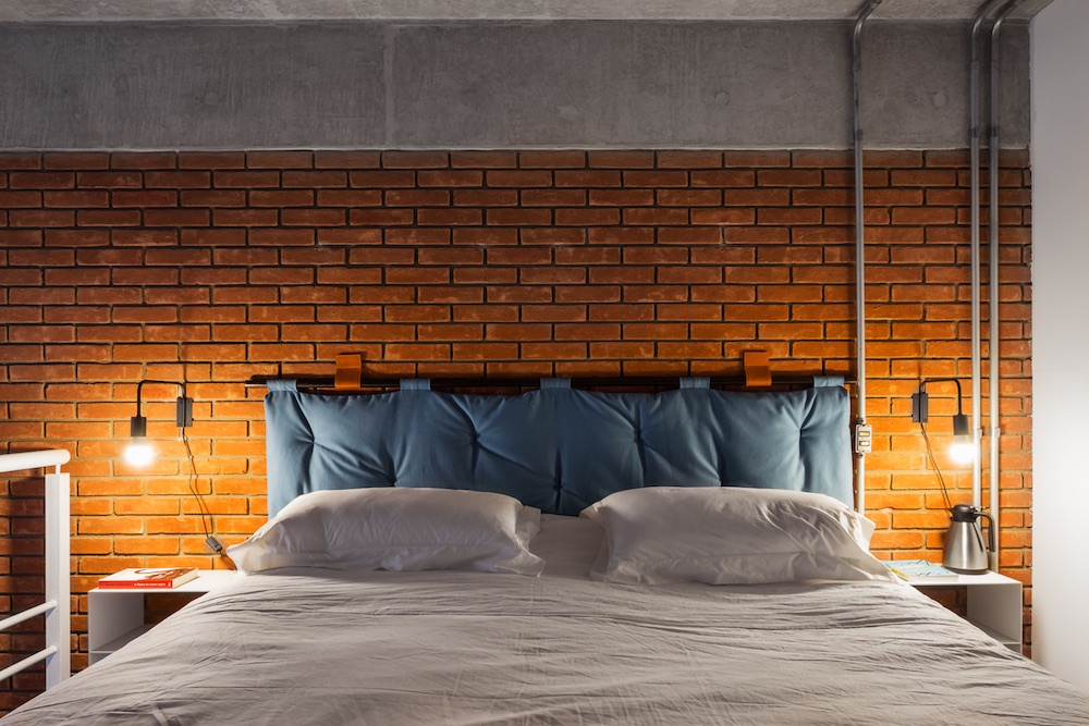 the bedroom has a large comfy bed with a blue upholstered headboard and industrial sconces