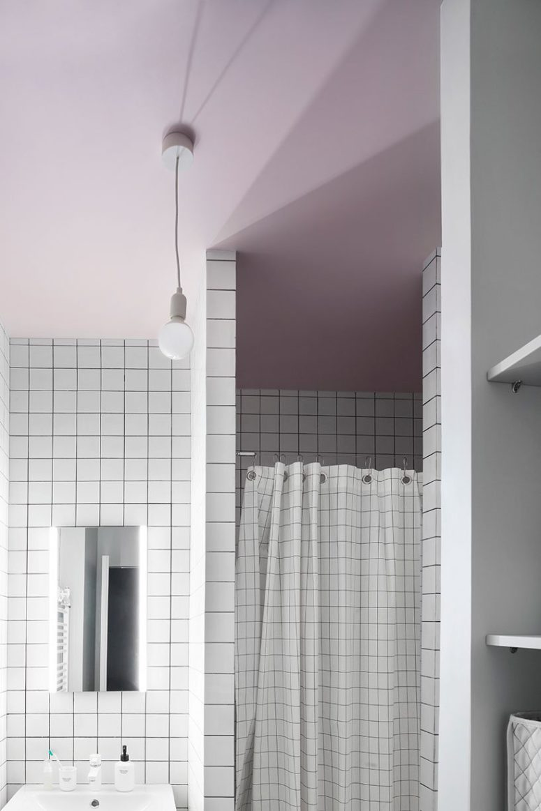 The bathroom is done with a pink ceiling and white tiles with black grout for a creative look