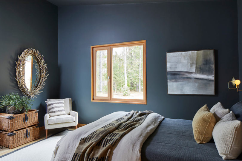The guest bedroom is done in graphite grey, antlers, wicker drawers