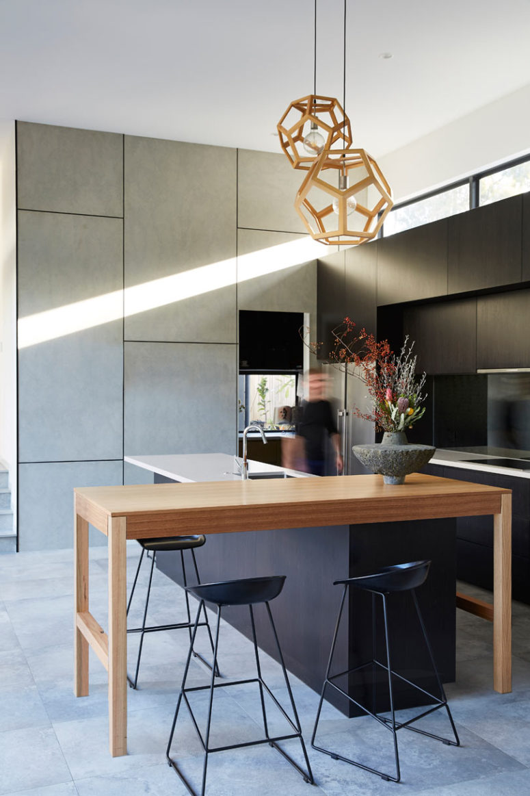 The kitchen is done with sleek grey and black cabinets, a wooden console table for having a meal and a kitchen island