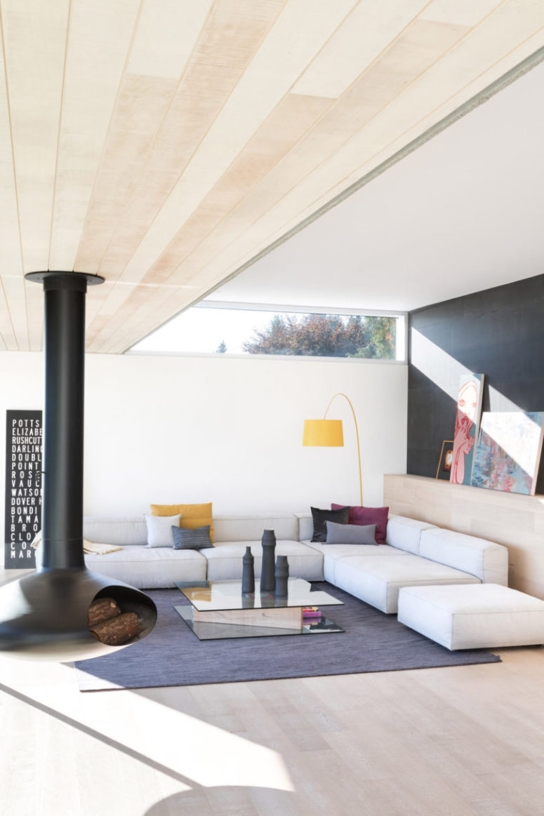The living room features a corner sofa, a glass coffee table, a hanging hearth and some colorful touches