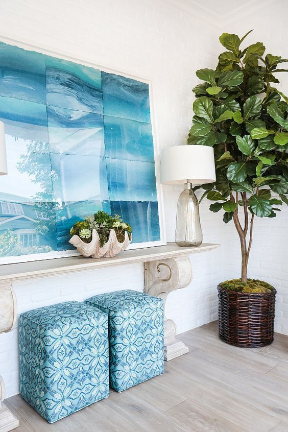 a beach-inspired console, a shell planter, a glass vase and a large seaside-inspired artwork