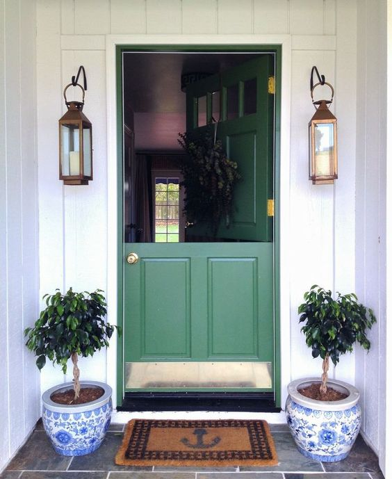 a chic green Dutch entrance door with brass touches, lanterns and pots for a cute look