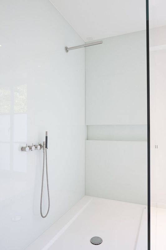 a chic white bathroom with a shower with a glass door and stainless steel touches