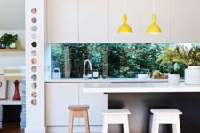 08 a contemporary black and white kitchen is spruced up with yellow lamps and a window backsplash