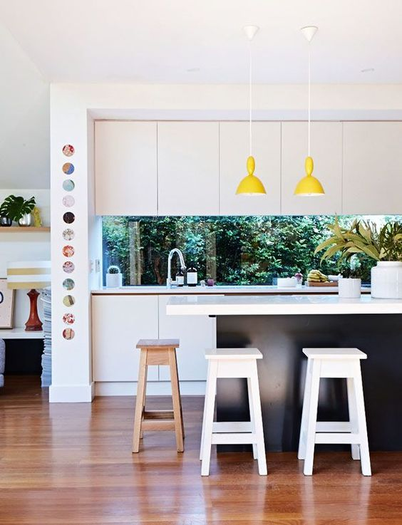 a contemporary black and white kitchen is spruced up with yellow lamps and a window backsplash