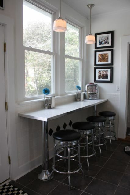 a small breakfast bar with a windowsill table and some industrial stools for a cozy feel