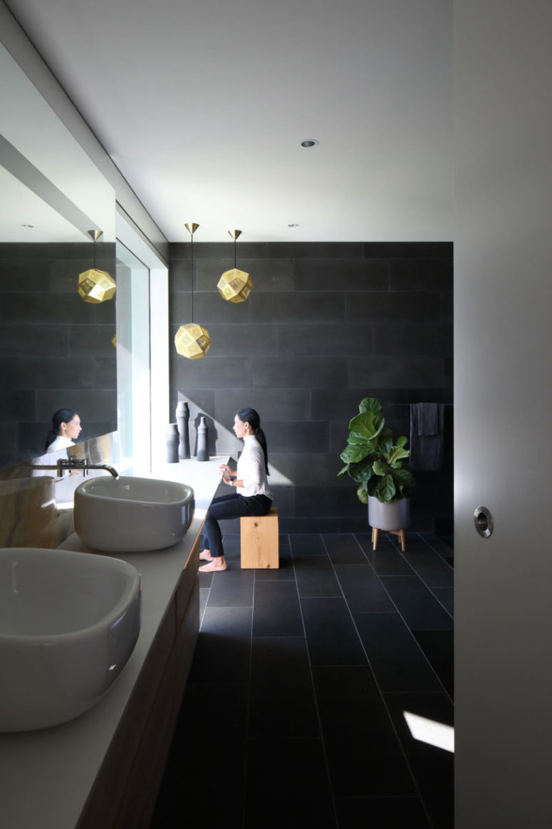 The bathroom is clad with dark tiles, sculptural sinks and some wooden touches for a spa feel