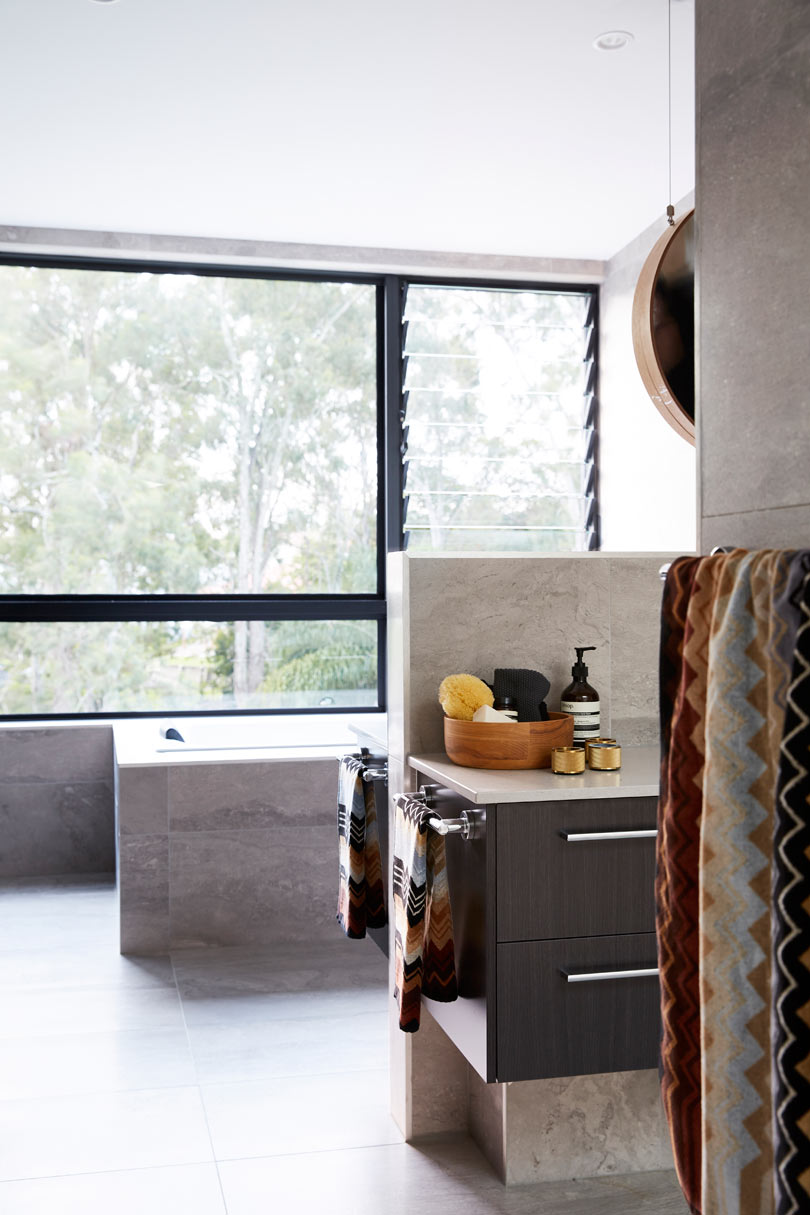 The bathroom is done with light colored stone, and the whole wall is glazed to enjoy the views and flood the space with light
