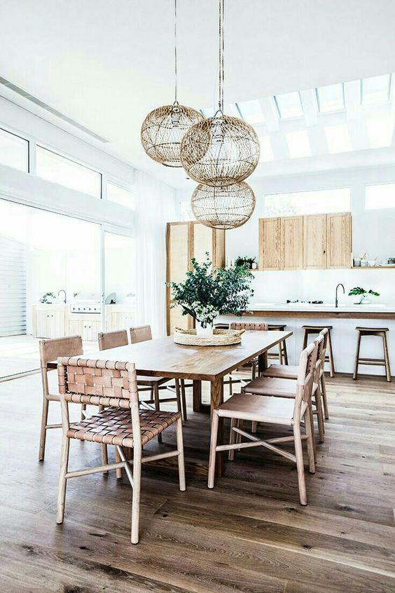 a boho beach dining space with wicker furniture and pendants looks very fresh and modern