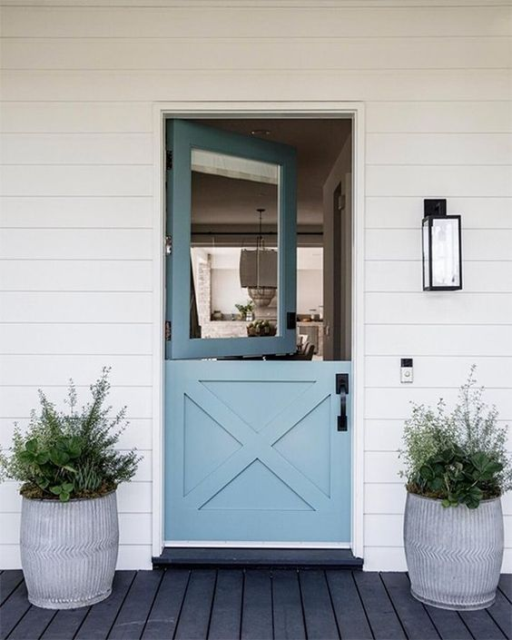 a contemporary beach entrance with a blue Dutch door and symmetrical pots with succulents