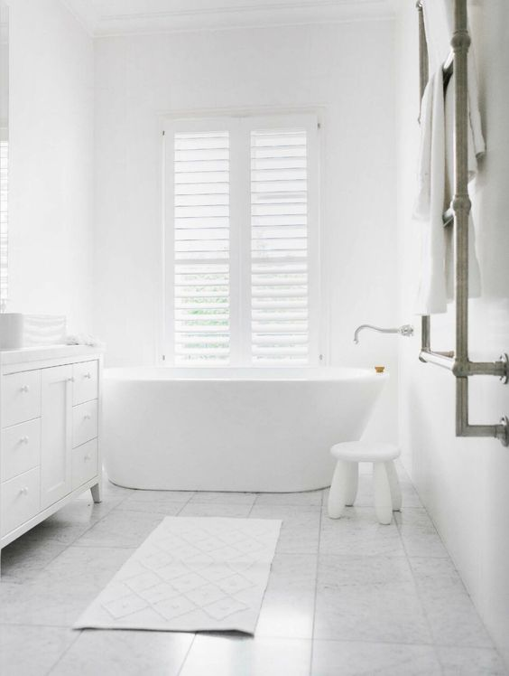 a minimalist all-white space with a stool, a large vanity and a free-standing bathtub