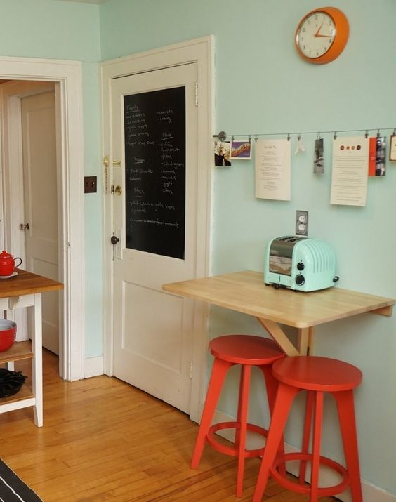 a tiny colorful breakfast bar with a wall-mounted table, red chairs and a blue toaster