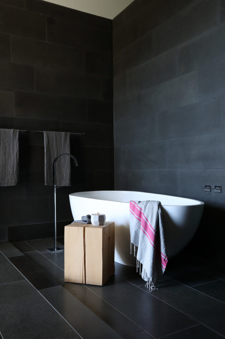 The bathtub is sculptural and a wooden slab side table contrasts with it