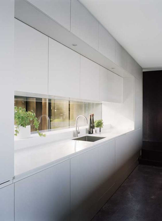 a minimalist kitchen in white with a window backsplash to give a touch of color and more interest to the space
