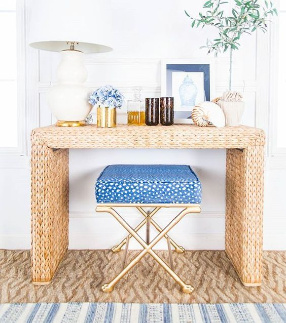 a straw console table, blue flowers, large shells, greenery and a blue chair for a beach feel