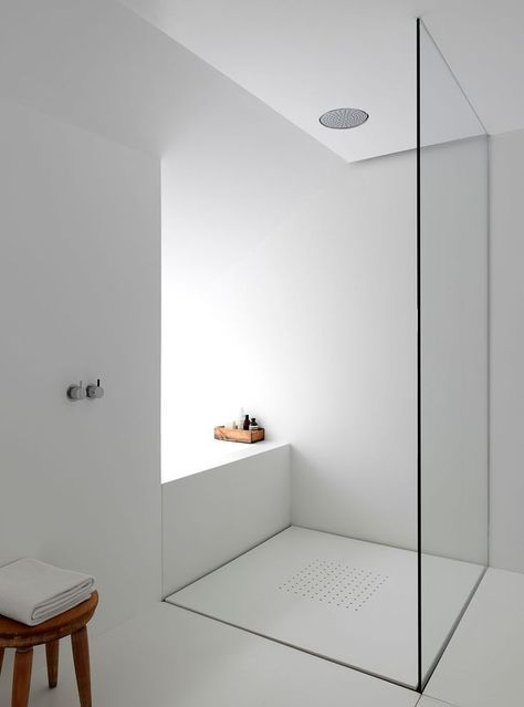 an ultra-minimalist bathroom in white with a glass shower and a wooden stool