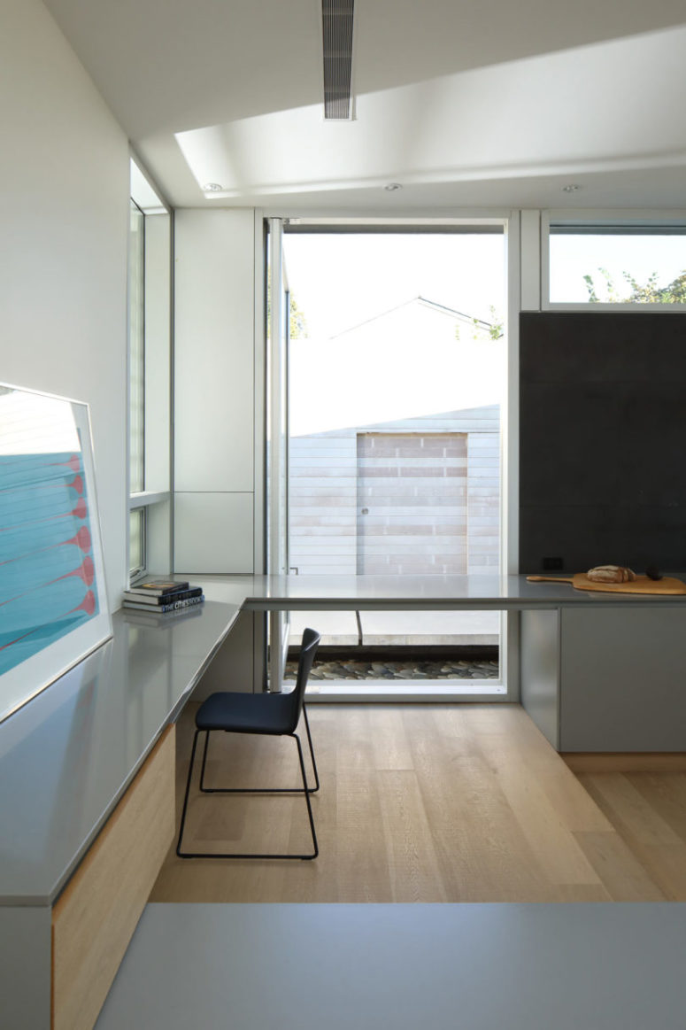 The home office is done with a corner desk and large windows to enjoy the courtyard views